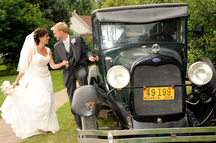 Portrait of a happy bride and groom next to an antique car