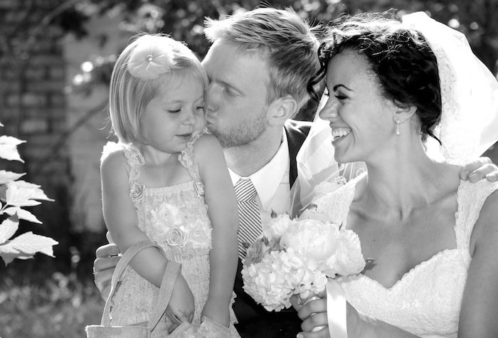 Bride and groom laugh and play with an adorable little girl.