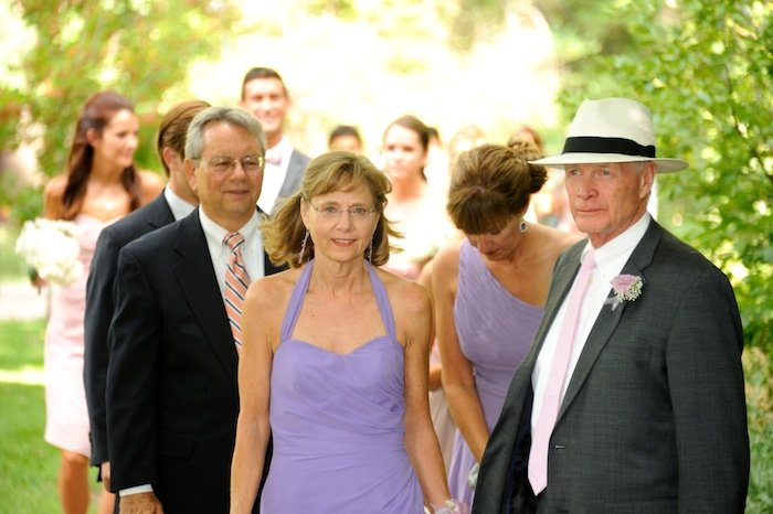 Groom's parents prepare to be seated at their son's wedding in Littleton, Colorado