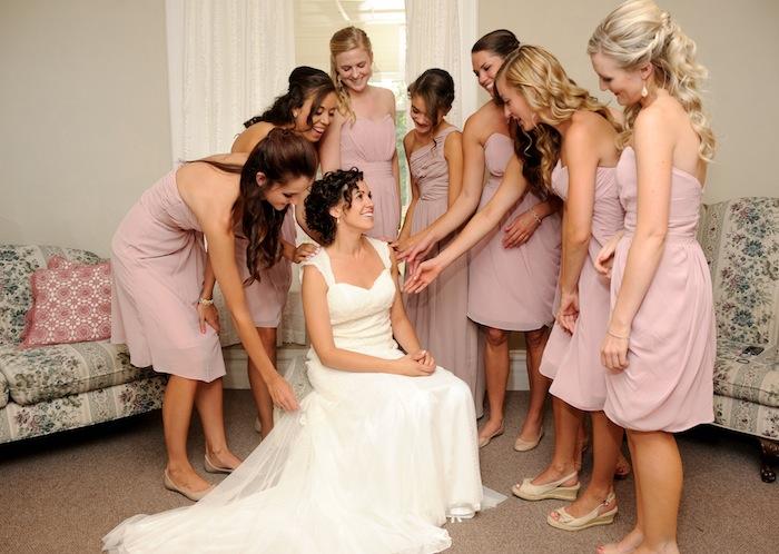 Pink-clad bridesmaids gather around bride smiling and happy on her Colorado wedding day