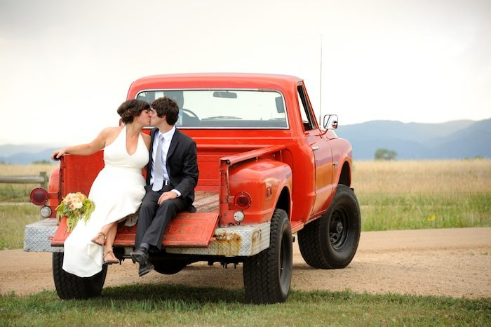 Bride and groom kissing seated on the tailgate of a red truck. beautiful-longmont-farm-wedding-hot-summers-day-kiefel-photography