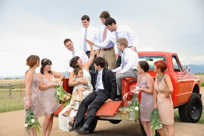 Creative group shot of the bridal party sitting on the back of a beautiful red truck outside in Longmont, Colorado. beautiful-longmont-farm-wedding-hot-summers-day-kiefel-photography