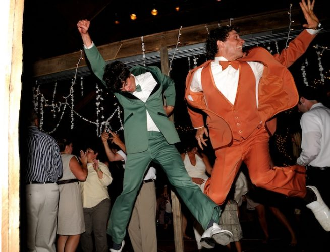 Two men in coordinated suits jump and dance at a wedding reception in Colorado. beautiful-longmont-farm-wedding-hot-summers-day-kiefel-photography
