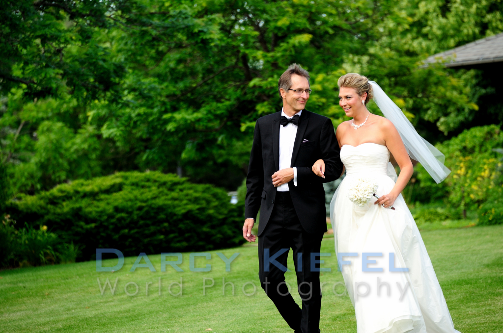 The father of the bride walking her down the aisle at the Boulder Country Club during a June wedding